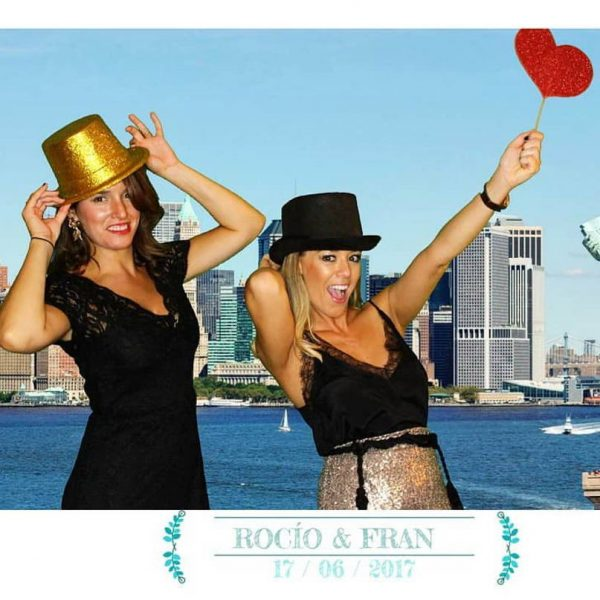 2 women in photobooth with a back ground photocall